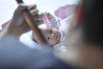 Ein Baby hört und schaut aufmerksam einem Gitarrenspieler zu