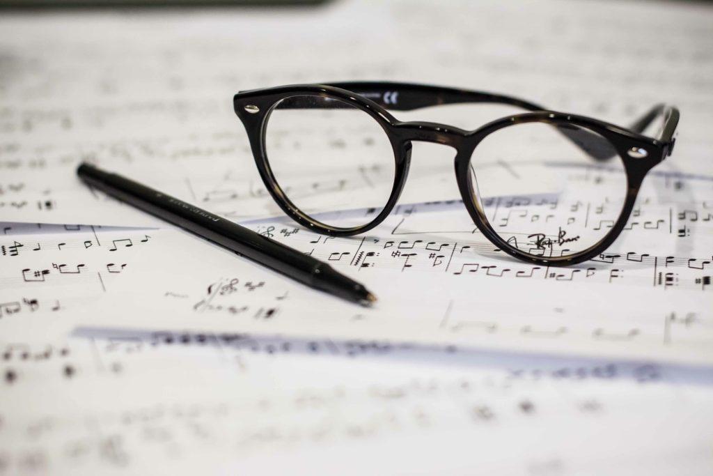 Brille und Stift auf Notenblättern - Songwriting